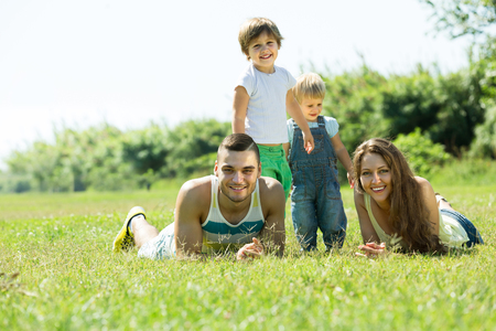 2 3 years: Happy family of four lying on grass in sunny summer park Stock Photo