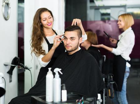 Felice giovane professionista parrucchiere facendo acconciatura per i giovani