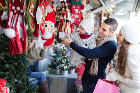 overcoat: Happy family choosing christmas decorations. A baby is touching a Santa Claus plush toy. Shallow focus. Focus on man Stock Photo
