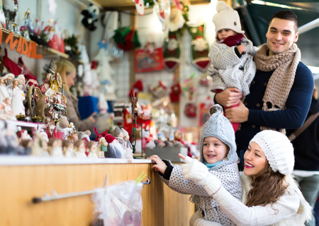 3 5 years: Beautiful casually dressed lady with her children and boyfriend smiling pointing at a counter with christmas decorations. Stock Photo