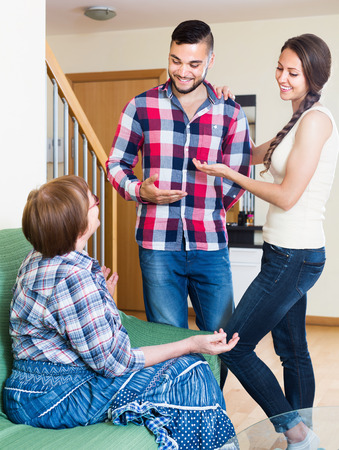 mother in law: Future married couple talking with his elderly mother Stock Photo