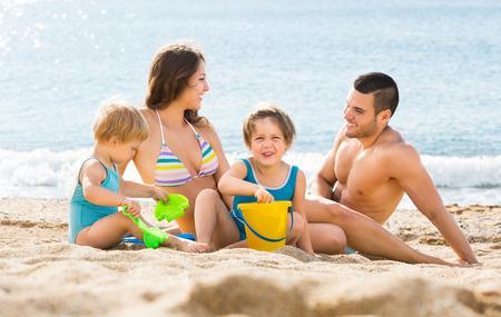 Familia alegre de cuatro sentado en la playa y jugando con la arena Foto de archivo