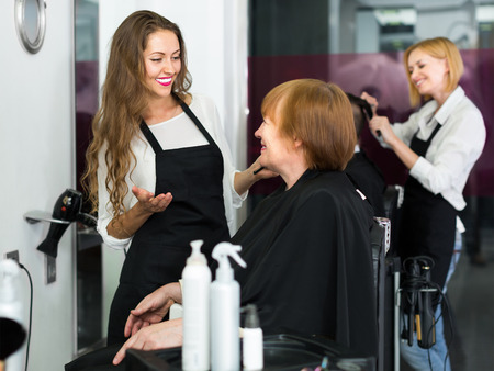 haircutter: Elderly woman talking about cuts hair with barber