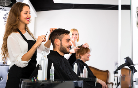 hairtician: Beautiful female hairdresser is making a modern haircut for a male customer