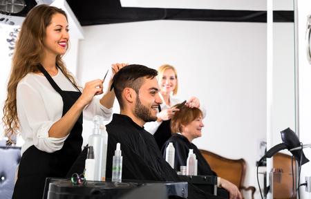 upsweep: Beautiful female hairdresser is making a modern haircut for a male customer