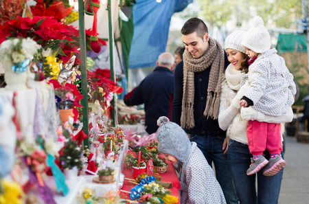 25 30 years: Smiling young parents with little girls at counter with Poinsettia. Shallow focus Stock Photo