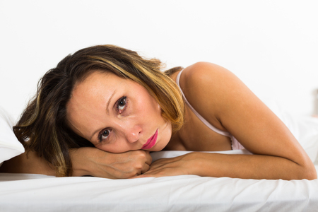 ennui: Unhappy middle-aged woman laying in bed with dropped eyes