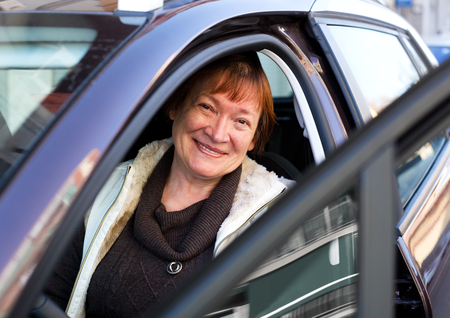 75s: Cheerful mature woman sitting in new car at driver seat