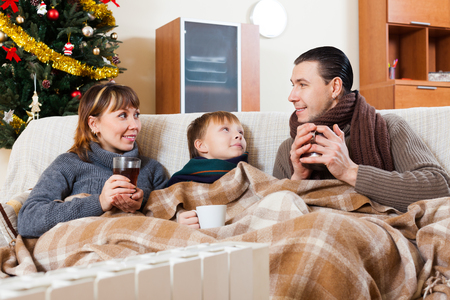 family of three with cups of tea warming near warm radiator in Christmas time Stock Photo