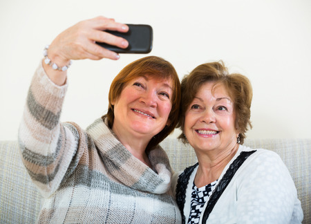 75s: Portrait of female pensioners making selfie on phone and smiling at home Stock Photo