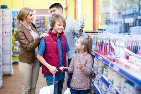 Average family with children buying tooth-brush in supermarket. Selective focus