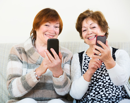 70 75: Smiling senior friends sitting with mobile phones in living room. Focus on right woman