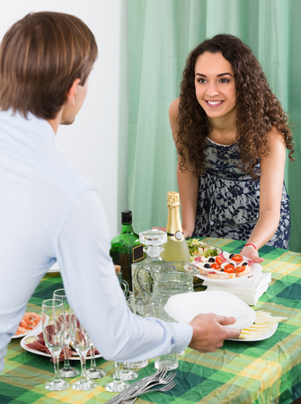 25 35: Cheerful smiling young couple preparing for guests visit at home Stock Photo