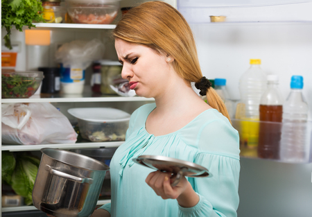 foul: unhappy woman noticed foul smell of food from casserole Stock Photo