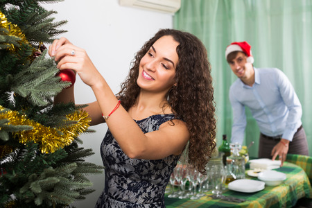 decorating christmas tree: Happy couple decorating Christmas tree and preparing table Stock Photo