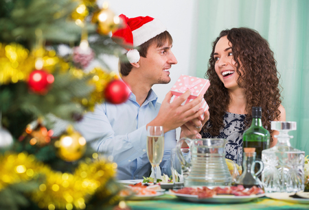 20 30 years: Man giving present to happy woman during Christmas dinner in home