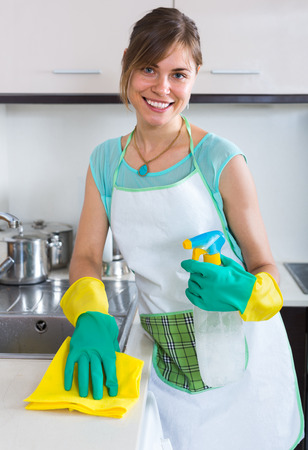 cleanup: Young positive maid doing professional clean-up in home kitchen Stock Photo