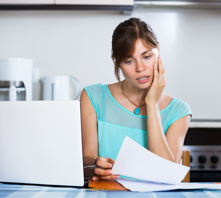 statement: Upset housewife reading banking statement Stock Photo