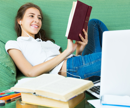 18 20: Positive female college student study in livingroom at home