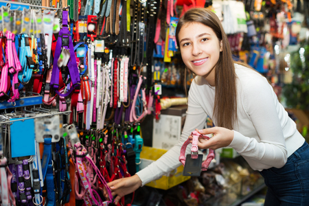 petshop: Happy girl selecting collars and leads in petshop