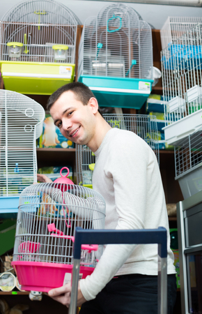 19's: Smiling young guy buying cage for bird in shop