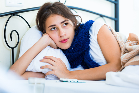 18 20: Sad teenage girl with high fever and flu in bed Stock Photo