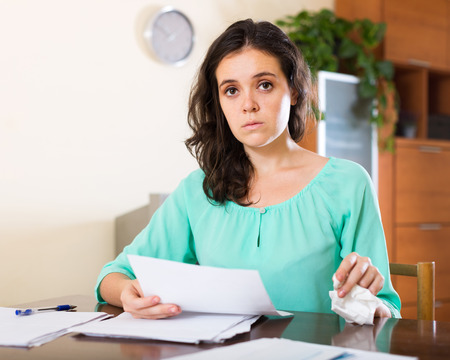 miserable: Unhappy woman calculating something at home