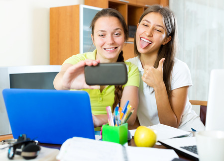 avocation: Two happy young girls taking a selfie photo on mobile phone while talking