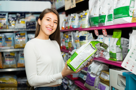 19's: Positive young brunette carefully choosing dry food fore home pet Stock Photo