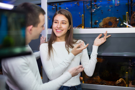 aquarian fish: Portrait of cheerful young couple watching tropical fish in petshop