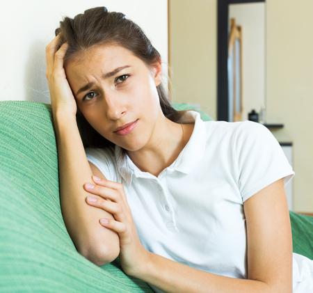 soltería: infeliz muchacha adolescente sola en el sofá en la sala de estar en casa