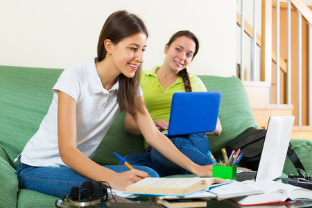 frendship: Positive teenage college student girls studying at home with books and computers