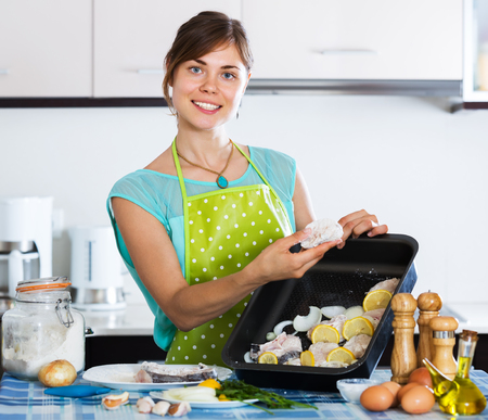 25 35: Happy woman preparing merluccid hake on baking sheet at home Stock Photo