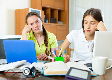 mournful: Two sad female students working on laptop computers. Focus on the left woman Stock Photo