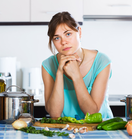 casalinga: Young housewife with sad face cooking dinner at home Archivio Fotografico