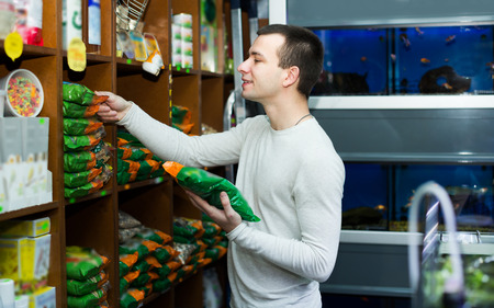 25 35: Happy young man watching diet products and smiling in pet store