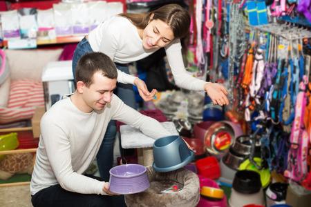 petshop: Portrait of happy couple purchasing pet bowls in petshop