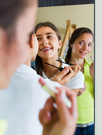 makeups: Smiling teenage girlfriends having fun while putting make up in front of mirror