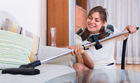cleanup: Smiling young woman doing regular clean-up and using hoover indoors