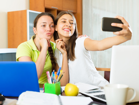 avocation: Student girls sitting at the table and making photo on the mobile phone at home