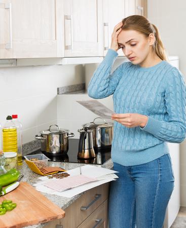 deprimida mujer joven con estados financieros listos para llorar