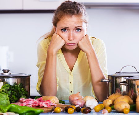 woman cooking: Unhappy housewife with meat and vegetables at kitchen table