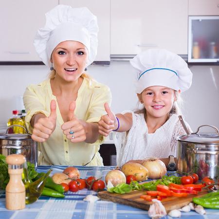vegeterian: happy russian mom and little daughter cooking vegeterian dish indoors