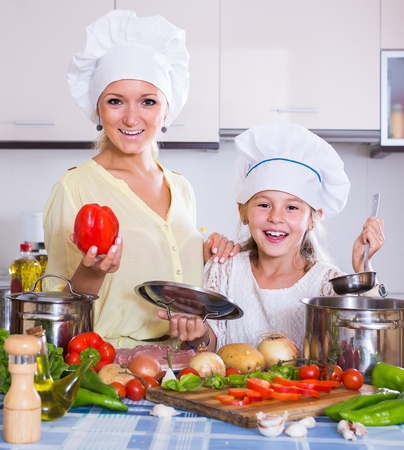 vegeterian: smiling russian mom and little daughter cooking vegeterian dish indoors