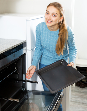 by placing: Attractive woman placing roasting tray in kitchen oven and smiling