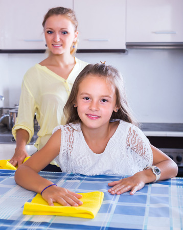 top 7: Smiling housewife and little girl cleaning together in kitchen