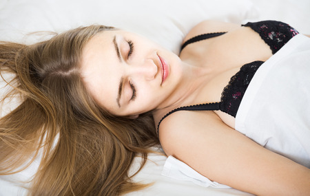 wellness sleepy: adult american woman lying in bed under sheet with closed eyes