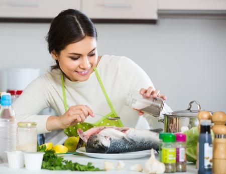 corcovado: Happy russian girl eviscerating salmon fish in domestic kitchen
