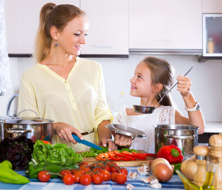 Happy young mother and little daughter preparing vegetables in slow-cooker Stock Photo