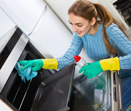 snuff: Smiling positive adult girl in gloves removing snuff in oven Stock Photo